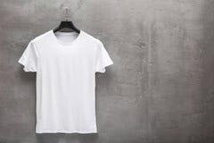 Främre sida av den manliga vita bomullst-skjortan på en hängare royaltyfria bilder