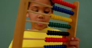 Främre sikt av afrikansk amerikanskolpojken som lär matematik med kulrammet i ett klassrum 4k lager videofilmer