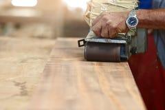 Främre sikt av bälteslipmaskinen som arbetar på ett styckträ med händer av arbetaren med kopieringsutrymme Selektivt fokusera och royaltyfria foton
