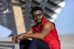 Främre sikt av bärande solglasögon för en ung svart man som sitter på trappuppgång i en solig dag, medan se bort arkivfoton