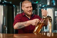 Främre sikt av bartendrar som arbetar i bar och hällande öl i exponeringsglas arkivfoto