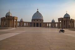 Främre sikt av basilikan av vår dam av fred med en bkeryttare som korsar förgården Arkivfoto