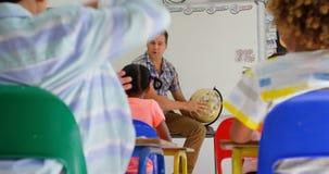 Främre sikt av Caucasian undervisande skolbarn för manlig lärare om jordklotet i klassrumet 4k stock video