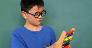 Främre sikt av den asiatiska skolpojken som löser matematikproblem med kulrammet i ett klassrum på skola 4k stock video