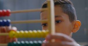Främre sikt av den asiatiska skolpojken som löser matematikproblem med kulrammet på skrivbordet i ett klassrum på skola 4k arkivfilmer