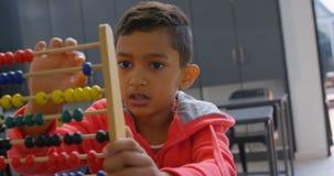 Främre sikt av den asiatiska skolpojken som löser matematikproblem med kulrammet på skrivbordet i ett klassrum på skola 4k stock video
