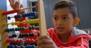 Främre sikt av den asiatiska skolpojken som löser matematikproblem med kulrammet på skrivbordet i ett klassrum på skola 4k lager videofilmer