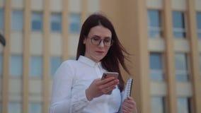 Främre sikt av den bärande vita skjortan för affärskvinna genom att använda en smart telefon på en stadsgata Ultrarapidskott stock video