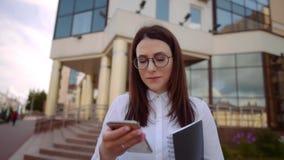 Främre sikt av den bärande vita skjortan för affärskvinna genom att använda en smart telefon på en stadsgata Ultrarapidskott lager videofilmer
