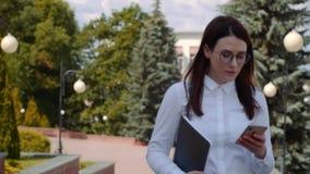 Främre sikt av den bärande vita skjortan för affärskvinna som går och använder en smart telefon på en stadsgata Ultrarapidskott lager videofilmer