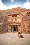 Främre sikt av den berömda alen-Khazneh (aka kassa) med kamel som vilar bredvid den i den forntida staden av Petra Arkivfoton