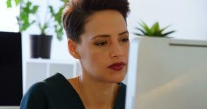 Främre sikt av den Caucasian affärskvinnan som arbetar på datoren på skrivbordet i ett modernt kontor 4k stock video