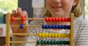 Främre sikt av den Caucasian skolflickan som lär matematik med kulrammet i klassrumet 4k arkivfilmer
