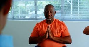 Främre sikt av den höga mannen för aktiv afrikansk amerikan som utför yoga i konditionstudion 4k stock video