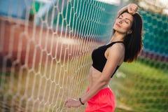 Främre sikt av den sexiga kvinnahållbollen i hand efter straff Målvaktställning i port bak stadion med platsen på bakgrund fe arkivfoton