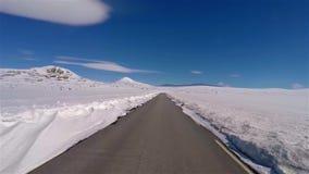 Främre sikt av den snöig vägen i Norge med blå himmel stock video