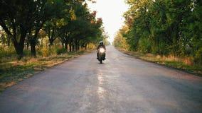 Främre sikt av den stilfulla mannen i svart motorcykel för hjälm- och läderomslagsridning på en asfaltväg på en solig dag in stock video