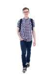 Främre sikt av den stiliga tonårs- pojken med ryggsäcken som går isolaten Royaltyfria Foton
