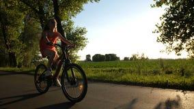 Främre sikt av den tonåriga flickan på en cykel under solnedgång stock video