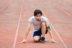 Främre sikt av den unga asiatiska idrottsman nenmannen som är klar att köra på spår i stadion sunt begrepp arkivbilder