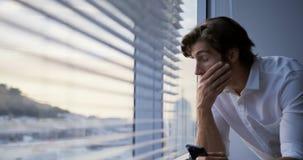 Främre sikt av den unga Caucasian manliga ledaren som använder mobiltelefonen nära fönster i det moderna kontoret 4k stock video