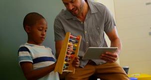 Främre sikt av den unga Caucasian undervisningskolpojken för manlig lärare som använder kulrammet i klassrumet 4k lager videofilmer