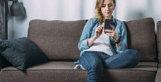 Främre sikt av den unga kvinnan i grov bomullstvillskjortan som hemma sitter på soffan och använder smartphonen Flickan använder  royaltyfria bilder