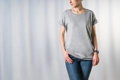 Främre sikt av den unga kvinnan, iklätt ljus - den gråa t-skjortan och jeans som står på ljus - grå bakgrund royaltyfri fotografi