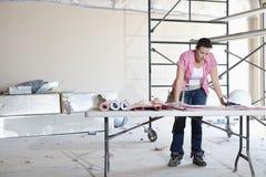 Främre sikt av den unga kvinnliga leverantören som ser byggnadsplan på tabellen Arkivbild