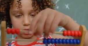 Främre sikt av denlopp skolflickan som lär matematik med kulrammet i ett klassrum på skola 4k arkivfilmer