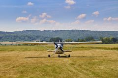 Främre sikt av det Cessna 172 flygplananseendet på gräsfält med blå molnig himmel på bakgrunden royaltyfri foto