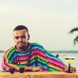 Främre sikt av det stiliga positiva mexicanska bartenderanseendet på th royaltyfri fotografi