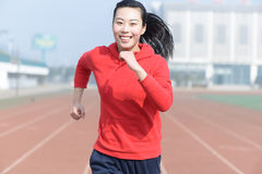 Främre sikt av en härlig idrottskvinnaspring in mot kamera Arkivfoto