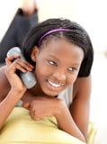 Främre sikt av en hållande ögonen på tv för afrikansk kvinna Royaltyfri Foto