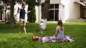 Främre sikt av en idyllfamilj som ut tillsammans hänger i parkera Ungt mammasammanträde på ett gräs och hålla ögonen på hans son stock video