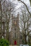 Främre sikt av en kyrka i mitt av en kyrkogård i England, Royaltyfri Foto