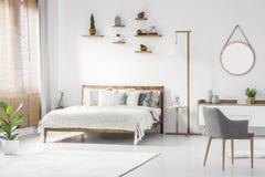 Främre sikt av en ljus naturlig sovruminre med träsäng royaltyfri fotografi