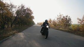 Främre sikt av en man i svart motorcykel för hjälm- och läderomslagsridning på en landsväg lager videofilmer