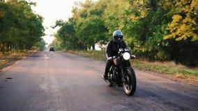 Främre sikt av en man motorcykel för ridning i för det gråa hjälm- och läderomslaget och för plädskjortan på en asfaltväg på soli stock video