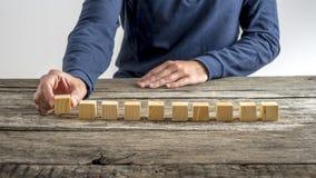 Främre sikt av en man som i rad förlägger tio träkuber Royaltyfri Foto