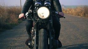 Främre sikt av en oigenkännlig man i svart motorcykel för ridning för läderomslag på en landsväg som rymmer ett styre bifokal arkivfilmer