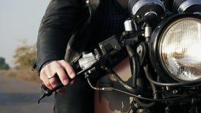 Främre sikt av en oigenkännlig man i svart motorcykel för ridning för läderomslag på en landsväg Stor billykta som vänds på arkivfilmer