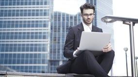 Främre sikt av en stilig ung affärsman som arbetar med en utomhus- bärbar dator hans kontor royaltyfri fotografi