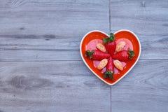 Främre sikt av enformad maträtt med jordgubbar och tangerin inom, på ett neutralt grått golv fotografering för bildbyråer