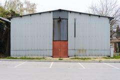 Främre sikt av ett järnlagringshus nära en parkering arkivfoto