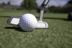 Främre sikt av golfbollen och puttern bak boll Royaltyfri Foto