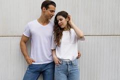 Främre sikt av härliga unga par som kramar, ser kameran och ler, medan stå utomhus arkivbilder