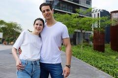 Främre sikt av härliga unga par som kramar, ser kameran och ler, medan stå utomhus arkivfoto