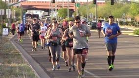 Främre sikt av löpare som deltar i en maraton arkivfilmer