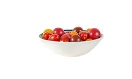 Främre sikt av lösa tomater i en bunke på vit bakgrund Arkivbilder